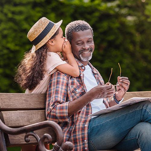 girl whispering to senior reading on park bench