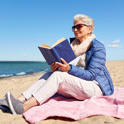 senior woman with sunglasses reading on beach